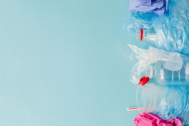 青色の背景にさまざまな種類の使い捨てのプラスチック廃棄物 Premium写真