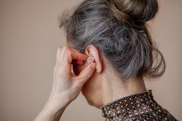 年配の女性が彼女の耳に補聴器を挿入します Premium写真