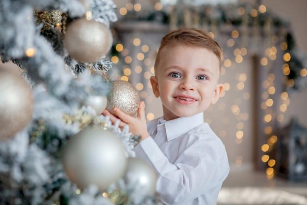 小さな男の子はクリスマスのためのクリスマスツリーを飾る Premium写真