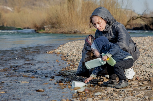 環境コンセプトを保存し、小さな男の子と母親がビーチでゴミやペットボトルを収集してゴミに捨てています。 Premium写真