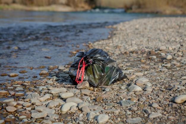 Загрязнение реки у берега, мусорный пакет у реки, пластиковые пищевые отходы, способствующие загрязнению Premium Фотографии