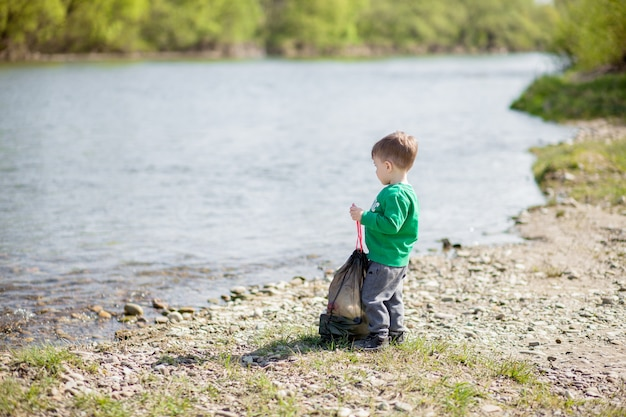 環境コンセプト、ビーチでゴミやペットボトルを収集する小さな男の子をゴミ箱に捨てる。 Premium写真