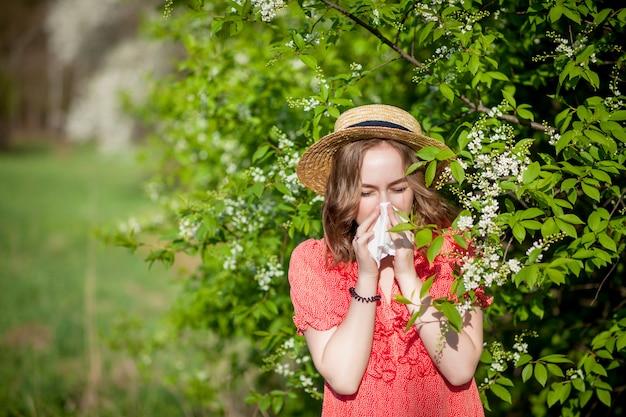 Молодая девушка сморкается и чихает в ткани перед цветущим деревом Premium Фотографии