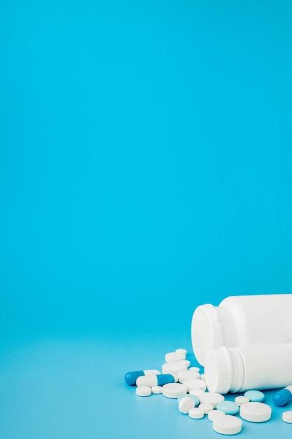 各種医薬品の丸薬、錠剤、カプセル、青の背景にボトル。テキスト用のコピースペース Premium写真