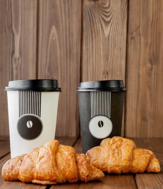 Бумажная чашка кофе и круассаны Premium Фотографии