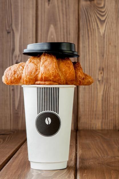 Бумажная чашка кофе и круассан Premium Фотографии