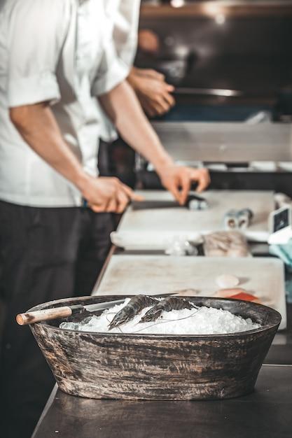 Креветки в миске. шеф-повар готовит суши. Premium Фотографии