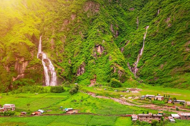 ネパールの滝と建物 Premium写真