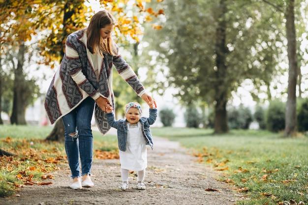 彼女の小さな娘が秋の公園にいる若い母親 無料写真