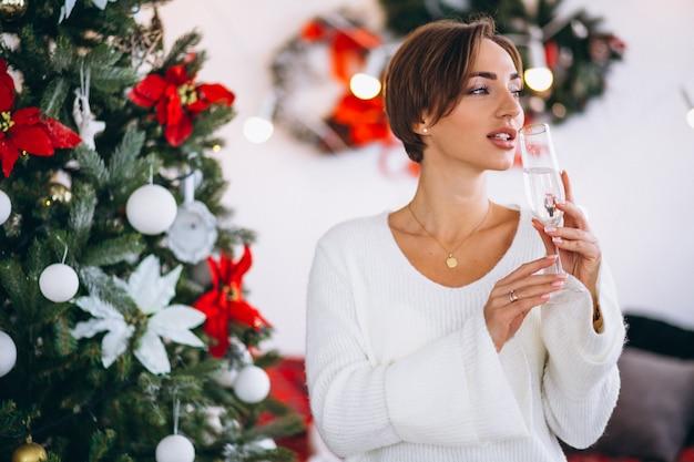 クリスマスツリーでシャンパンを飲む女性 無料写真