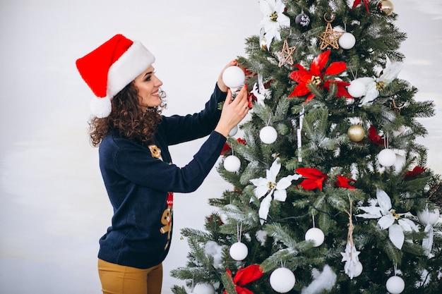 クリスマスツリーを飾る女性 無料写真