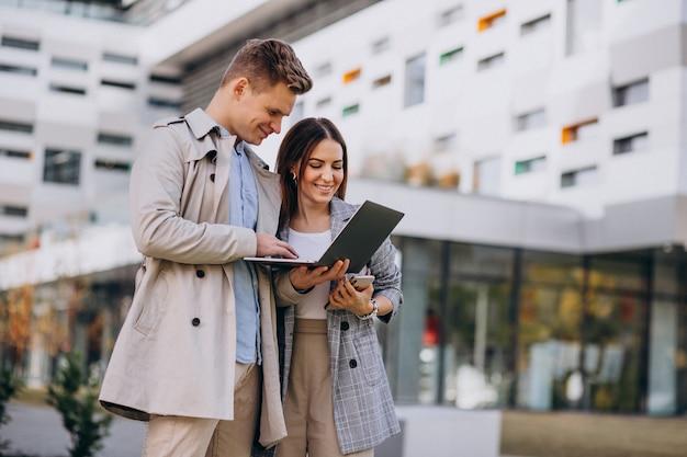 若いカップルが一緒に外に立っているとコンピューターを使用して 無料写真