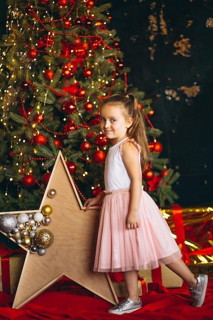 Маленькая девочка на рождество в розовом платье, стоя у елки Бесплатные Фотографии
