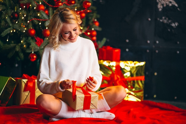 クリスマスツリーの贈り物を開梱する若い女性 無料写真