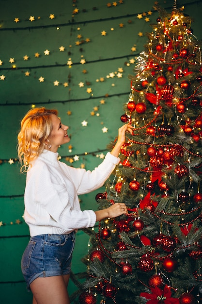 若い女性のクリスマスツリーを飾ること 無料写真