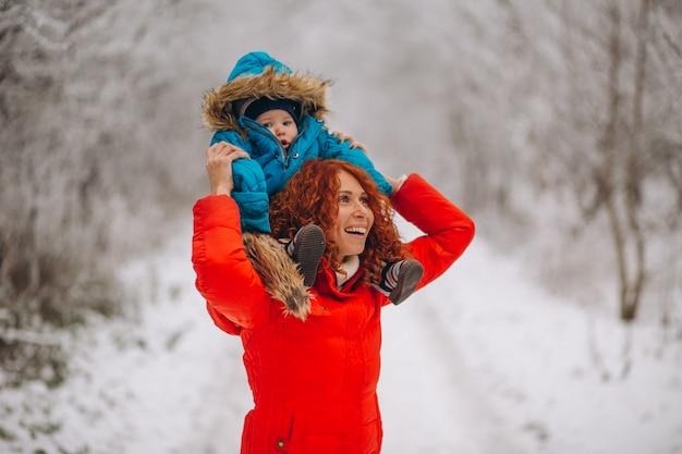 冬の公園で一緒に彼女の幼い息子を持つ母 無料写真
