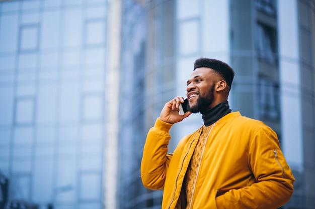アフリカ系アメリカ人学生が通りを歩いていると電話で話しています。 無料写真