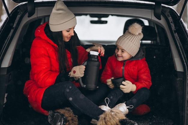 冬に車に座っている娘を持つ母 無料写真