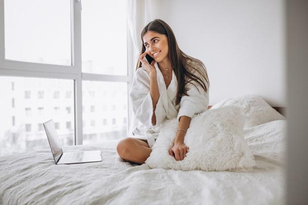 ベッドの中でコンピューターで作業して電話で話している女性 無料写真