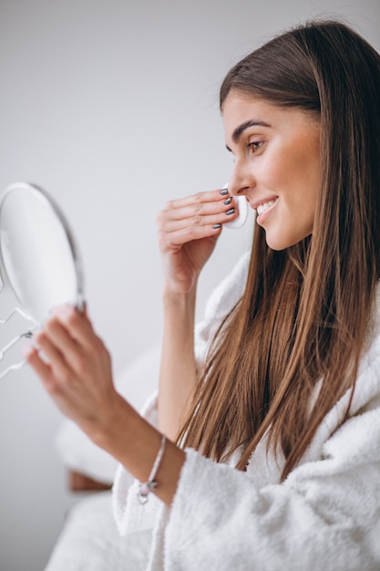 パッドと化粧を削除する鏡を持つ女性 無料写真
