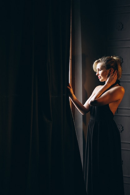 窓のそばに立っている黒いドレスの女 無料写真