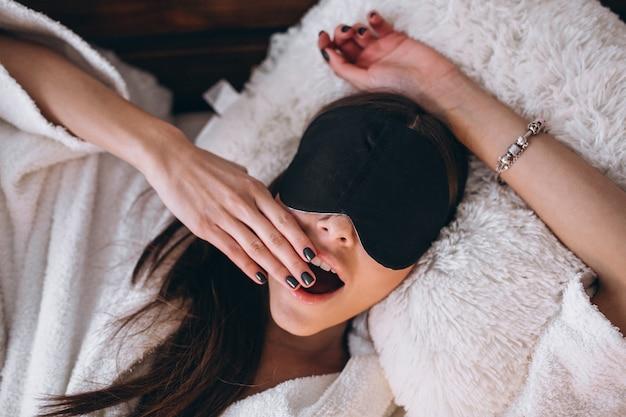 Женщина в кровати носить маску сна Бесплатные Фотографии