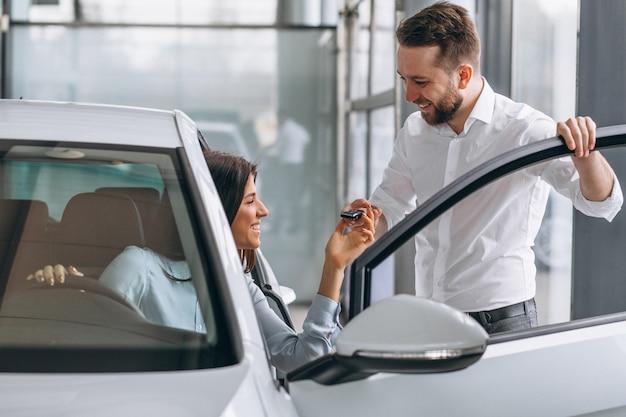 セールスマンと車のショールームで車を探している女性 無料写真