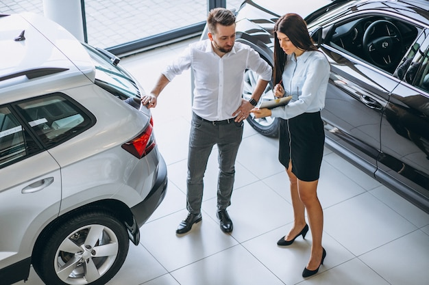 Продавец и женщина ищут машину в автосалоне Бесплатные Фотографии