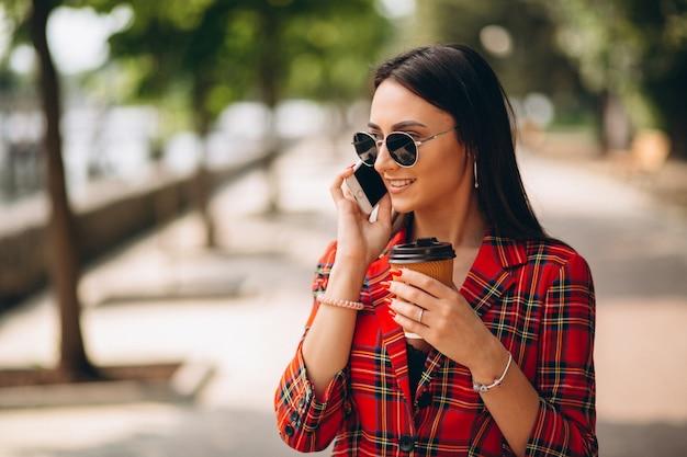 コーヒーを飲みながら電話で話している若い女性 無料写真