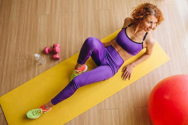 マットの上に横たわる女性フィットネストレーナー 無料写真