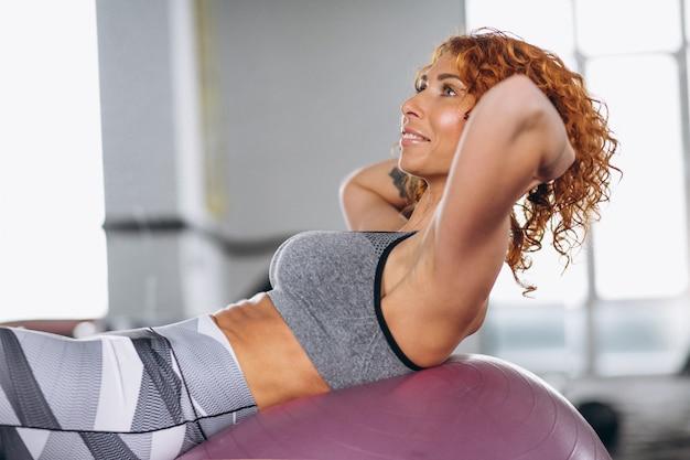 ジムでボールに腹筋をしているフィットネス女性 無料写真