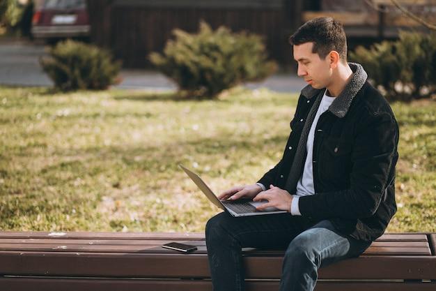 公園でラップトップを使用してベンチに座っているハンサムな男 無料写真
