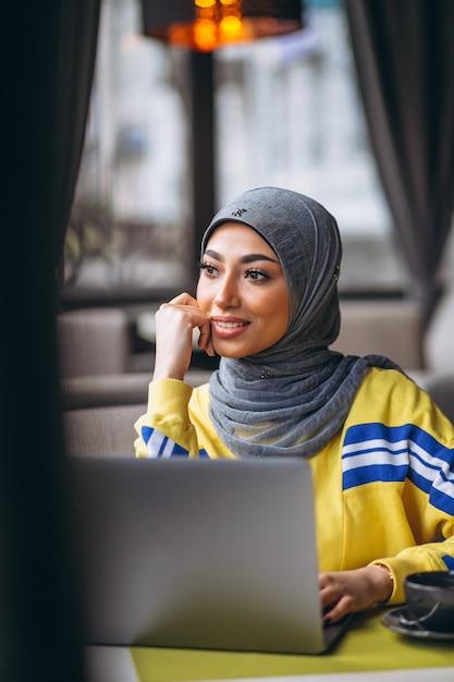 ラップトップに取り組んでいるカフェの中のヒジャーブのアラビア女性 無料写真