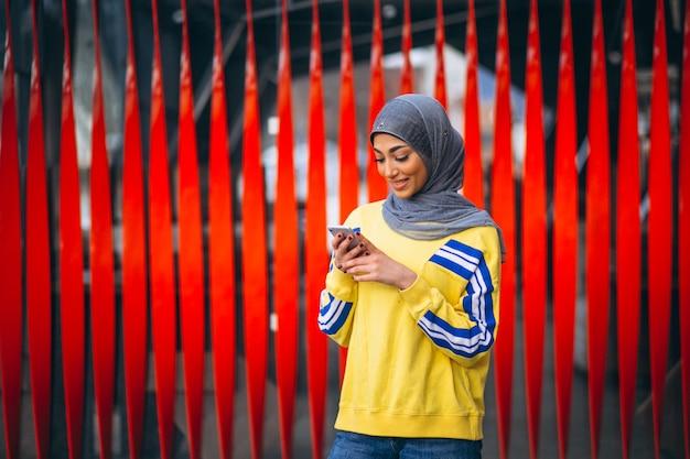 電話を使用して通りにヒジャーブの外でアラビアの女性 無料写真