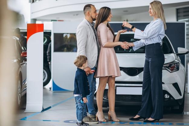 Семья с сыном, выбирая автомобиль в автосалоне Бесплатные Фотографии