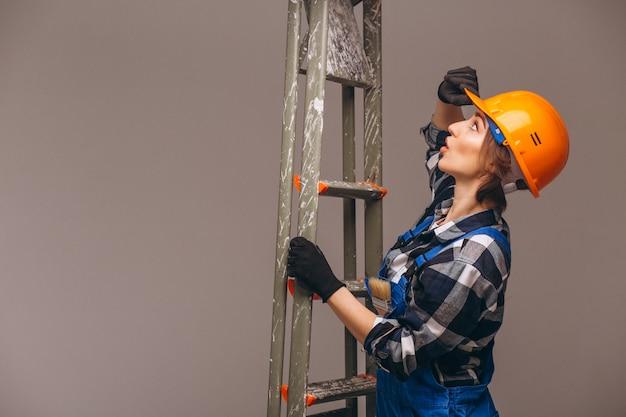 Женщина-ремонтник с лестницей в униформе Бесплатные Фотографии