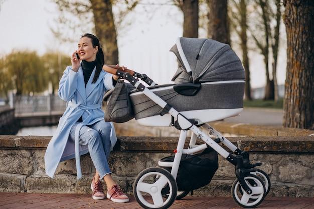 ベビーカーと公園で座っている若い母親 無料写真