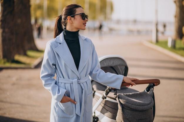 ベビーカーを公園で歩く若い母親 無料写真