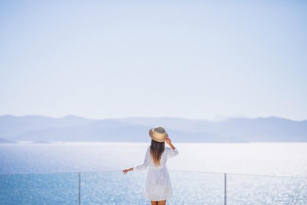 後ろから立っていると海を見ている若い女性 無料写真