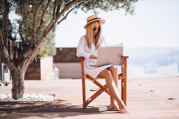 Молодая женщина работает на ноутбуке в отпуске Бесплатные Фотографии