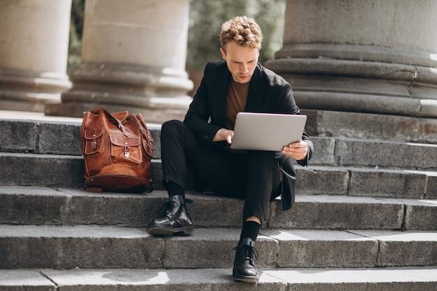 Молодой человек, работающий на компьютере в университете Бесплатные Фотографии