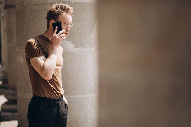 電話を使用して眼鏡でハンサムな男 無料写真