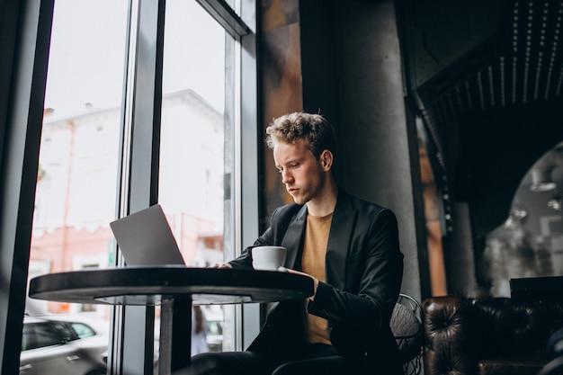 Красивый мужчина работает на компьютере в кафе и пить кофе Бесплатные Фотографии