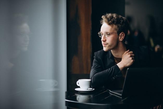 ハンサムな男がカフェでコンピューターに取り組んでいるとコーヒーを飲む 無料写真