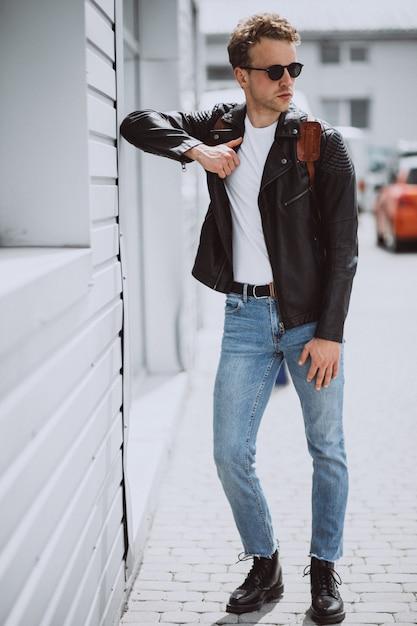 通りでポーズをとって若いハンサムな男モデル 無料写真