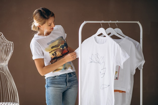 白いシャツを選ぶ女性 無料写真