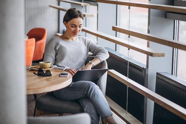 コーヒーを飲みながら、コンピューターに取り組んでいるカフェに座っている女性 無料写真