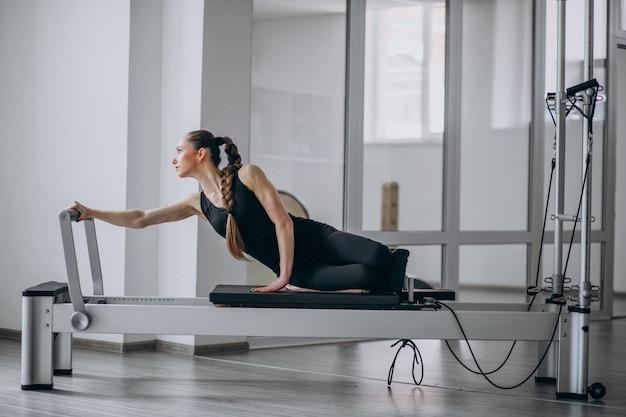ピラティスリフォーマーでピラティスを練習する女性 無料写真