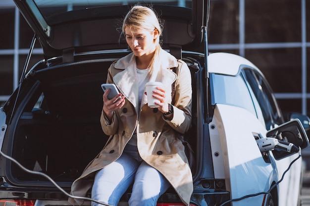 Женщина заряжает электро автомобиль на заправке Бесплатные Фотографии