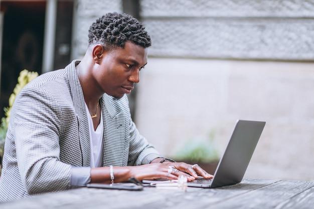 アフリカ系アメリカ人のビジネスマン、カフェでラップトップを使用して 無料写真